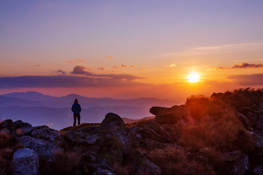 Tourist watching sunset in the mountains