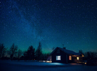 Photo sur Aluminium Bleu nuit Cottage against the night sky with the Milky Way and the arctic Northern lights Aurora Borealis in snow winter Finland