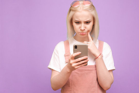 Funny blonde girl in cute clothes with a thoughtful face uses a smartphone on a purple background, the focus on the phone in the hands of the girl. Copyspace
