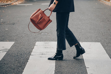 fashion blogger autumn 2019 outfit details. fashionable woman wearing black jeans, black ankle shoes a brown tan trendy leather handbag. crossing the street. detail of a perfect fall fashion outfit.