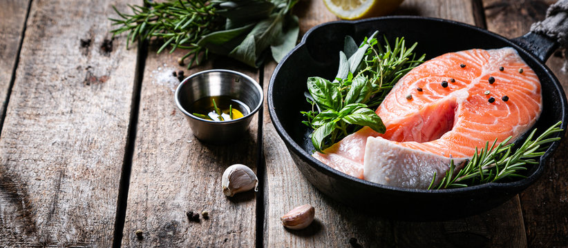 Raw salmon with herbs and spices, rustic background, copy space