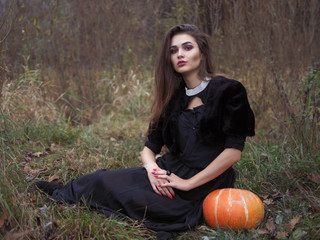 Young beautiful brunette witch in long black dress posing in the dreamy fall meadow with a pumpkin Wall mural