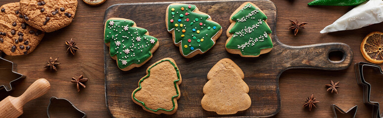 top view of glazed Christmas cookies with pastry bag on wooden cutting board, panoramic shot