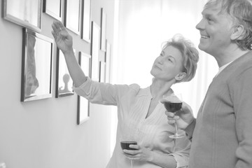 Mature woman showing off paintings on wall while drinking wine