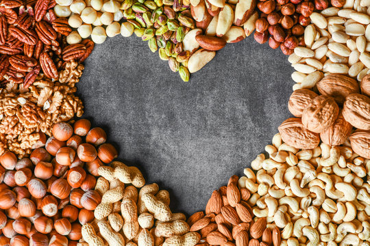 Natural healthy background made from different kinds of mixed nuts like walnuts, hazelnut, pistachio, almond, cashew, pecans. Heart shape top view.