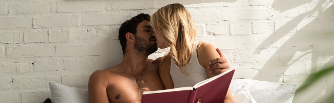 tender couple kissing and holding book in bed in the morning