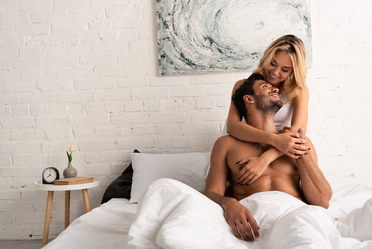 happy young couple hugging in bed in the morning