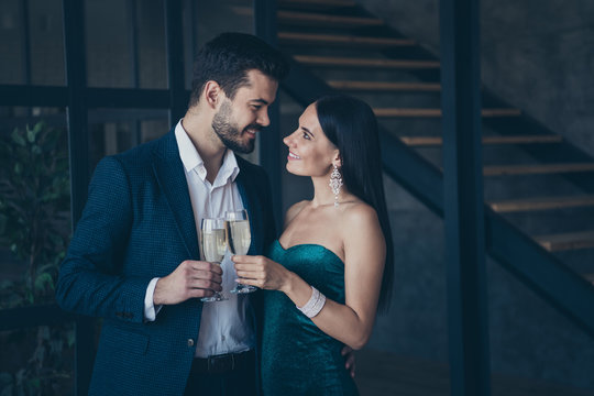 Profile photo of two people couple affectionate guy and lady standing close looking eyes drinking sparkling golden wine wear fancy formalwear suit dress indoors