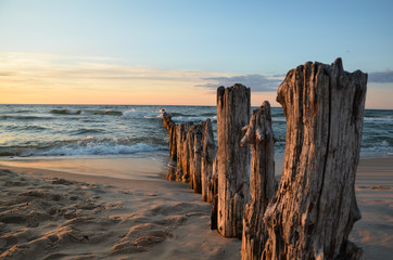 Wooden breakwater during sunset over the Baltic Sea, Uniescie, Poland.