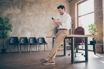 Full body profile side photo of confident smart middle eastern joyful businessman using smartphone send message to work colleagues partners feel content wear style pants trousers in loft office