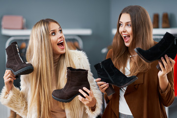 Adult women shopping for shoes in boutique in autumn