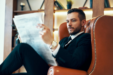 Confident young businessman reading newspaper and latest news while sitting in armchair