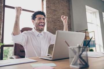 We got new partnership yes. Portrait of crazy delighted middle eastern arabian businessman sit desktop got message on computer about start-up success scream yeah raise fists in loft workplace