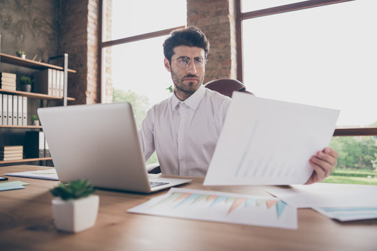 Portrait of thoughtful middle eastern man agent sit table in loft company office have computer look in charts analyze start-up statistics workstation progress