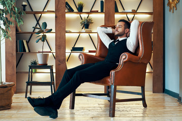 Confident young man relax in armchair in luxury interior