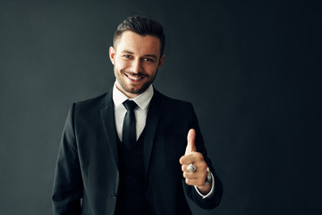Smiling young man in suit showing thumbs up sign on black background