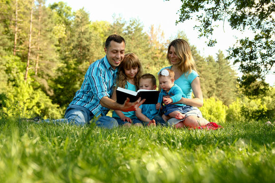 happy family reading the Bible in nature