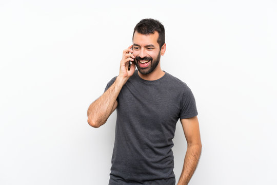 Young handsome man over isolated white background keeping a conversation with the mobile phone