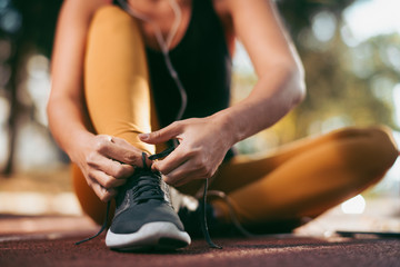 Young woman working out. Athlete woman getting ready for jogging.  Close up