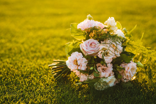 Beautiful weddin bouquet made of fresh pink roses on the grass suring sunset