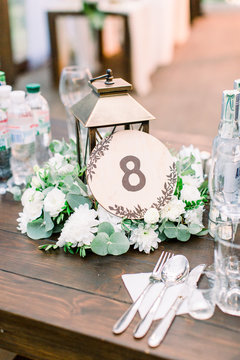 wedding table number and decor in rustic style. wedding decorations for table in rustic style, wooden desk, golden lantern and floral composition