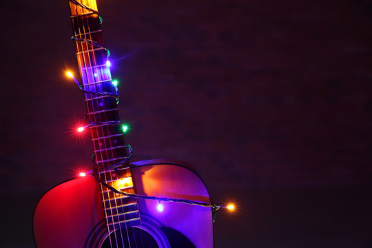 Acoustic guitar with Christmas lights against dark background