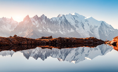 Poster Mountains Incredible view of clear water and sky reflection on Chesery lake (Lac De Cheserys) in France Alps. Monte Bianco mountains range on background. Landscape photography, Chamonix.