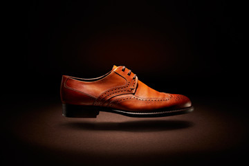 flying brown leather shoe