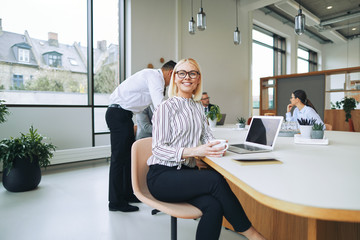 Smiling young businesswoman sitting in a boardroom drinking coff