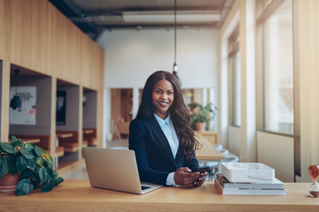 Smiling African American businesswoman working alone in an offic