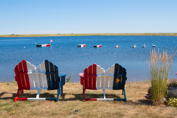 Acadian flag painted chairs and boats in New Brunswick Canada