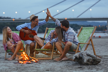 Group of friends sitting around camp fire at the beach at the autumn evening.They play guitar and...