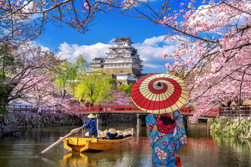 Wall Mural - Asian woman wearing japanese traditional kimono looking at cherry blossoms and castle in Himeji, Japan.