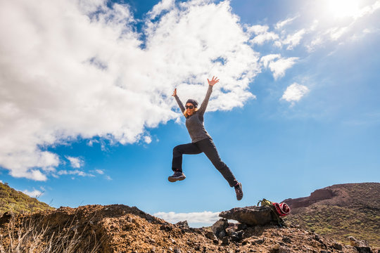 Happy healthy lifestyle woman smile and jump at the mountains having fun in trekking adventure activity - freedom and independence for people in the nature outdoor park