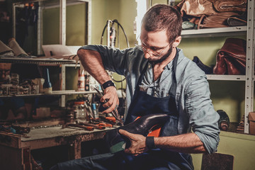 Talented cobbler is working on pair of black men's shoes at his workshop.