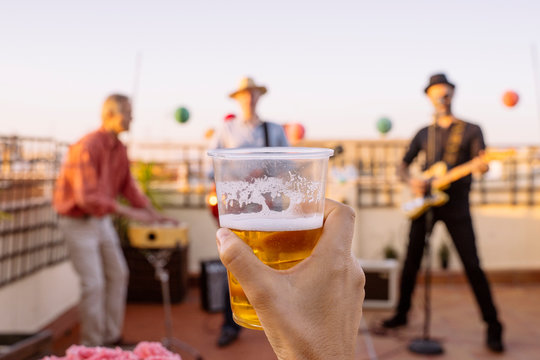 Unrecognizable woman lifting and cheering with a cold beer on intimate concert. Detail of a lager glass cheering with friends. Music and live concerts concept. Intimate music group with summer vibes.