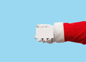 Santa Claus hand holding plastic credit card over isolated blue background.