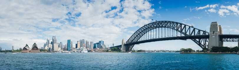 Photo sur Plexiglas Sydney A large panorama of Habour Bay with views of city of Sydney, Opera House and Habour Bridge on a blue sky. With white clouds