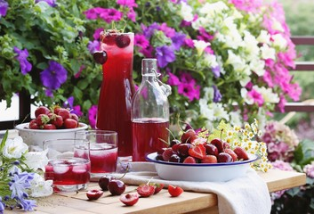 Summer berry cold drink. Iced drink from fresh seasonal berries on bright floral background.