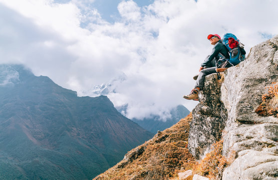 Young hiker backpacker female sitting on cliff edge and enjoying the Imja Khola valley during high altitude Everest Base Camp (EBC) trekking route near Phortse, Nepal. Active vacations concept image.