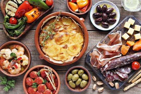 Spanish tapas. Traditional mediterranean appetizer table concept included tortilla, grilled vegetables, meatballs, garlic king prawns,olives and cured meat.