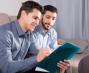 Two happy men with documents on sofa