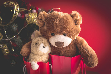 Christmas card with Teddy and bunny in red gift bags under the Christmas tree.  With  holiday decoration and presents