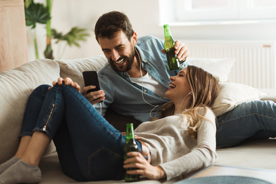 Young couple enjoying in MP3 music while drinking beer at home