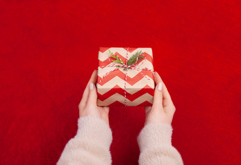 Woman holding Christmas presents on a Red table background...