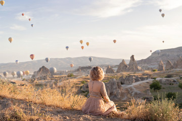 Poster Cappuccino woman is watching on scenery view with rising balloons on sunrise. Girl in gorgeous pink long dress sit on hill looking at large number of air balls. Fabulous Cappadocia mountains landscapes Turkey