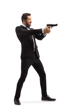 Man in a suit aiming with a gun