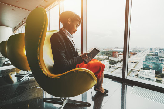 Side view of a dazzling young African-American woman entrepreneur sitting with a digital tablet on a yellow curved armchair indoors of a luxurious office room on a top floor of a business skyscraper