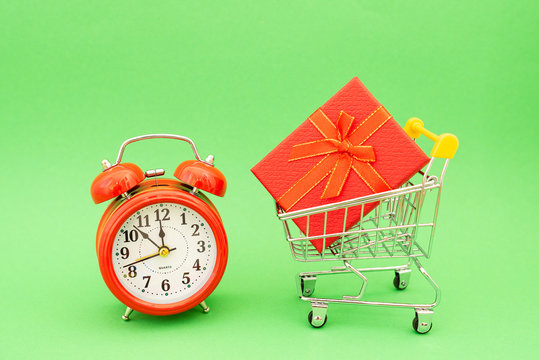 Christmas: gift box with red alarm clock on green background, gifts for the holidays , last minute Christmas shopping