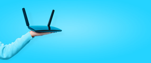 black wifi router on hand over blue background, panoramic mock up image